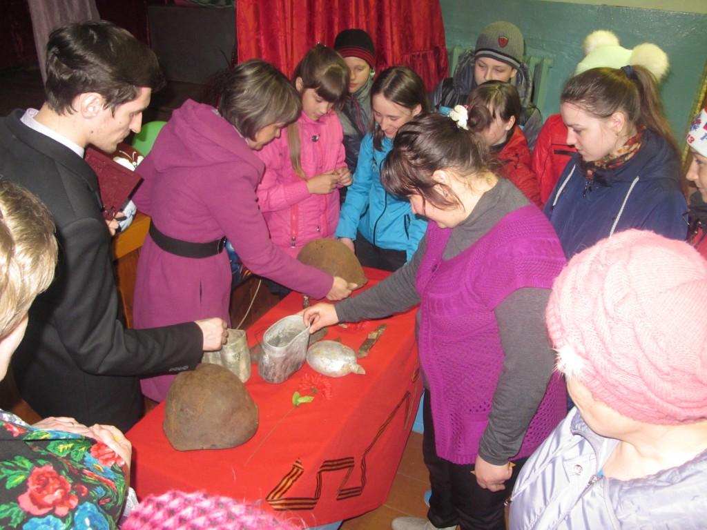 Жители с. Орехов Лог Краснозёрского района рассматривают военные артефакты